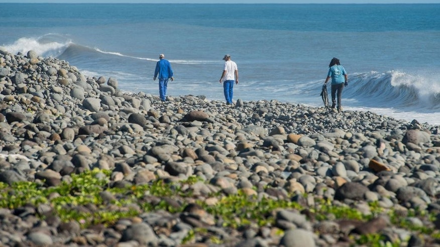 Municipal workers search Reunion Island beaches where expected debris of the missing Malaysia Airlines Flight 370 could be washed up onto the shore near Saint-Andre, Reunion island. The Malaysian plane disappeared on March 8, 2014, while flying from Kuala Lumpur, Malaysia, to Beijing, China. (AP Photo/Fabrice Wislez)