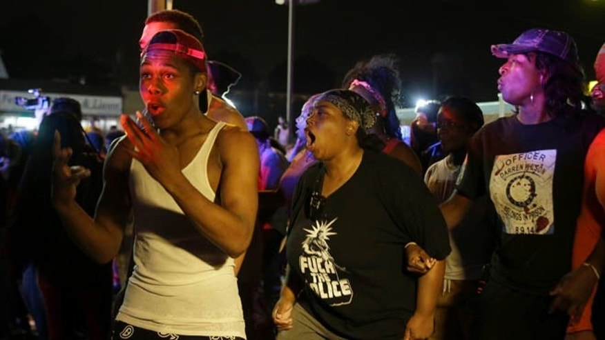 Protesters yell at police, Sunday, Aug. 9, 2015, in Ferguson, Mo., before shots were fired near the protest. The one-year anniversary of Michael Brown's death in Ferguson began with a march in his honor and ended with a protest that was interrupted by gunfire. (AP Photo/Jeff Roberson)