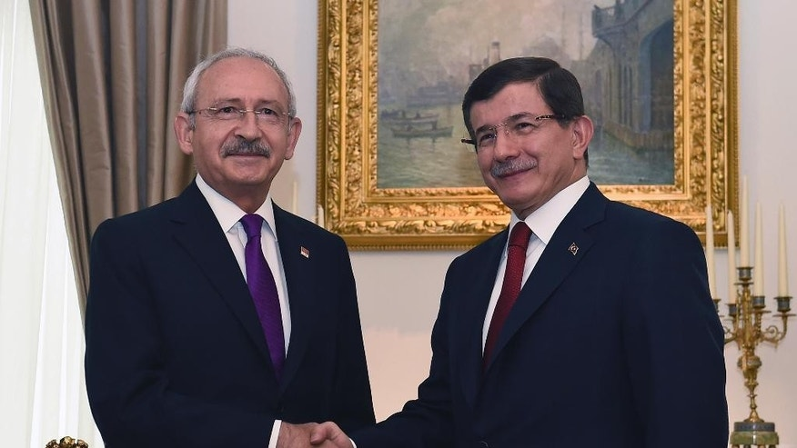 Turkish Prime Minister and leader of Justice and Development Party (AKP) Ahmet Davutoglu, right, shakes hands with the leader of the main opposition Republican People's Party (CHP) Kemal Kilicdaroglu, left, prior to their meeting regarding possible coalition government between the two parties, in Ankara, Turkey, Monday, Aug. 10, 2015. Davutoglu's Islamic-rooted ruling party lost its parliamentary majority in elections in June, forcing it to seek a coalition partner. Turkey has until Aug. 23 to form a new government before new elections have to be called. (AP Photo)