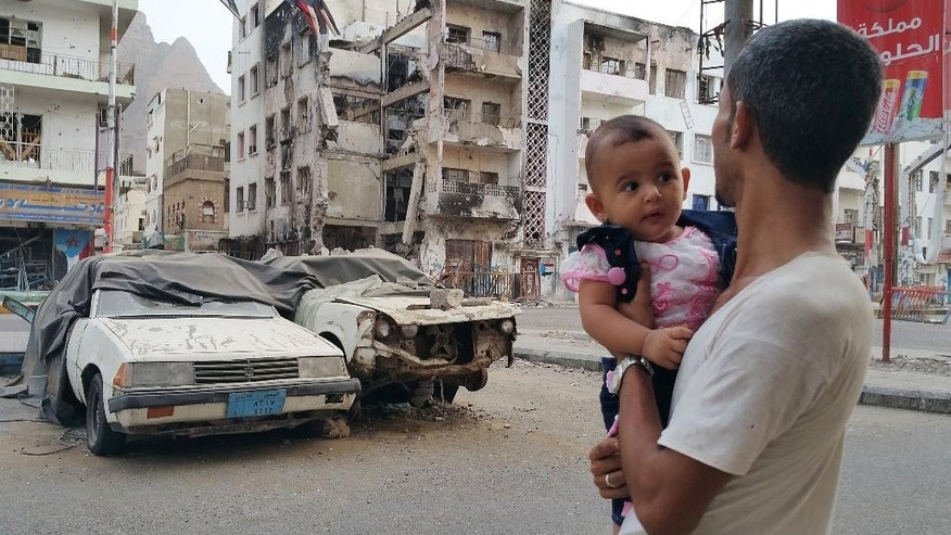 FILE - In this Sunday, July 19, 2015, file photo, a Yemeni man carrying his daughter looks at a building destroyed during fighting against Houthi fighters in the port city of Aden, Yemen. The international group Doctors Without Borders (Medecins Sans Frontieres) says it has treated more than 10,000 war-wounded in Yemen since March and that aid groups are being overwhelmed by the country's massive humanitarian needs. (AP Photo/Ahmed Sameer, File)