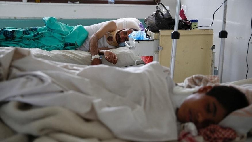 In this Saturday, Aug. 1, 2015, file photo, a man injured in a recent Saudi-led airstrike, background, lies on a hospital bed to receive treatment in Sanaa, Yemen. The international group Doctors Without Borders (Medecins Sans Frontieres) says it has treated more than 10,000 war-wounded in Yemen since March and that aid groups are being overwhelmed by the country's massive humanitarian needs. (AP Photo/Hani Mohammed, File)