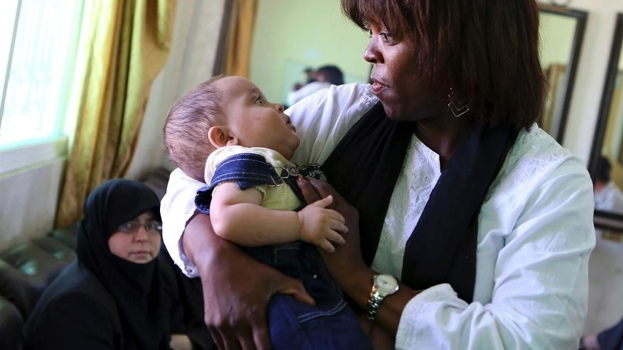 "In this Monday, Aug. 10, 2015, photo, World Food Program executive director Ertharin Cousin holds a Syrian refugee child while meeting with Syrian refugees in Amman, Jordan. Funding prospects are ""bleak"" and impoverished Syrian refugees face more cuts in food aid, the head of the World Food Program said in an interview, after inspecting the bare refrigerator of a refugee family and meeting boys forced to swap school for work to help their families survive. (AP Photo/Raad Adayleh)"