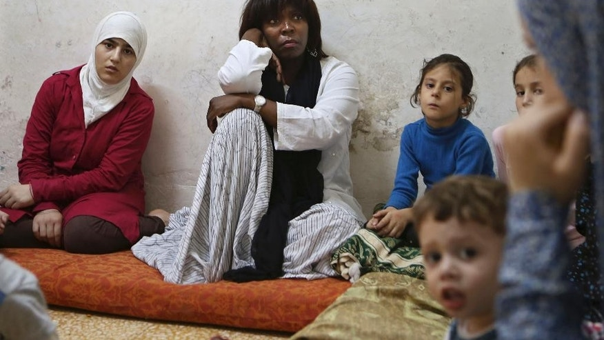 "In this Monday, Aug. 10, 2015, photo, World Food Program executive director Ertharin Cousin, center, listens while visiting a Syrian refugee family living in a one-room shelter in Amman, Jordan. Funding prospects are ""bleak"" and impoverished Syrian refugees face more cuts in food aid, the head of the World Food Program said in an interview, after inspecting the bare refrigerator of a refugee family and meeting boys forced to swap school for work to help their families survive. (AP Photo/Raad Adayleh)"