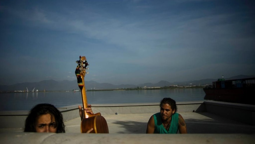 In this July 27, 2015 photo, people spend the morning on the new Malecon of Santiago, Cuba. Residents stroll along a recently completed harbor promenade under gleaming new streetlights, enjoying sea breezes while relaxing on newly installed metal benches, but what's missing are tourists. (AP Photo/Ramon Espinosa)