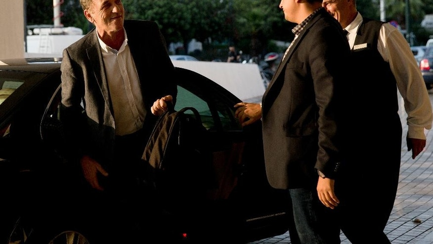 Greece's Economy Minister Giorgos Stathakis, left, arrives at a hotel to continue talks with bailout negotiators, in central Athens, on Monday, Aug. 10, 2015. Athens and the negotiators are hoping to conclude talks Tuesday for a third bailout package. (AP Photo/Petros Giannakouris)