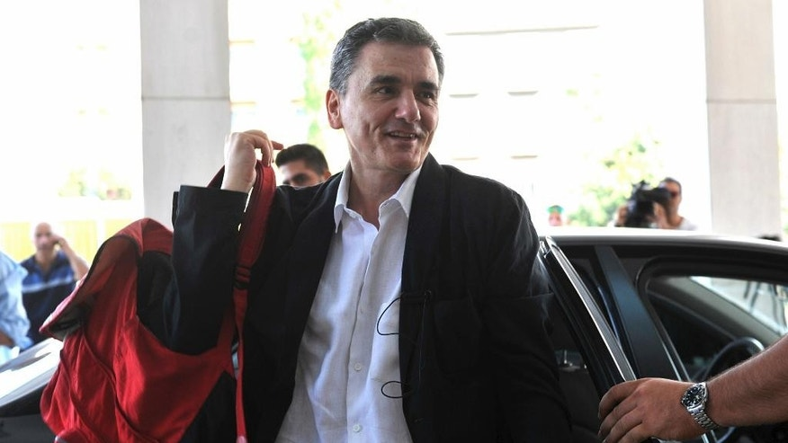 In this Friday, July 31, 2015 file photo, Greek Finance Minister Euclid Tsakalotos arrives for a meeting with senior negotiators at a hotel in Athens. Greece has essentially concluded its bailout talks with its creditors, with just a few details remaining for the deal to be formally clinched, Greek officials said Tuesday, Aug. 11. (Giannis Kotsiaris/InTime News via AP, File)  GREECE OUT
