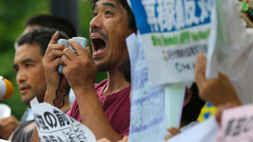 A protester shouts slogans during an anti-nuclear rally in front of Prime Minister's official residence in Tokyo, Tuesday, Aug. 11, 2015. Kyushu Electric Power Co. said Tuesday, it had restarted the No. 1 reactor at its Sendai nuclear plant as planned. The restart marks Japan's return to nuclear energy four-and-half-years after the 2011 meltdowns at the Fukushima Dai-ichi nuclear power plant in northeastern Japan following an earthquake and tsunami. (AP Photo/Shizuo Kambayashi)