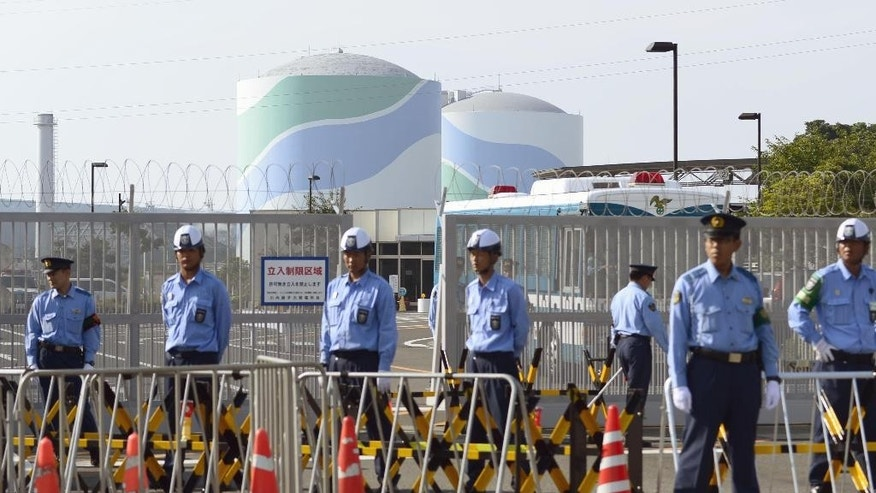 Police officers and security guards stand in front of the main gate to the the Sendai Nuclear Power Station as No. 1 reactor, left, and No. 2 reactor stand in Satsumasendai, Kagoshima prefecture, southern Japan, Tuesday, Aug. 11, 2015. With the pull of a lever, control rods were lifted Tuesday from the No. 1 reactor core at the plant, ending a ban on nuclear power following meltdowns in Fukushima that forced tens of thousands of people to leave their homes, most of them for good. (Hiroko Harima/Kyodo News via AP) JAPAN OUT, MANDATORY CREDIT