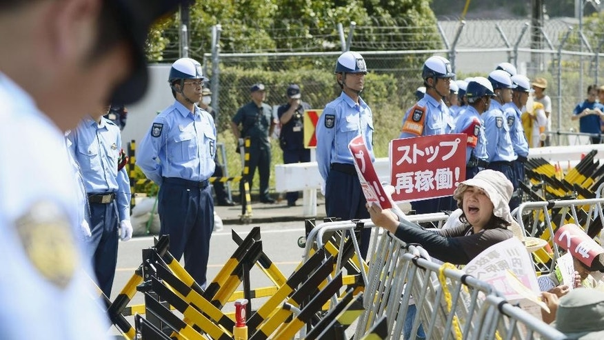 "A woman protester, holding a banner reading: ""stop (nuclear plant) resumption,"" shouts anti-nuclear slogans as security guards and police officers stand in front of the barricaded main gate to the the Sendai Nuclear Power Station in Satsumasendai, Kagoshima prefecture, southern Japan, Tuesday, Aug. 11, 2015. With the pull of a lever, control rods were lifted Tuesday from the No. 1 reactor core at the plant, ending a ban on nuclear power following meltdowns in Fukushima that forced tens of thousands of people to leave their homes, most of them for good. (Hiroko Harima/Kyodo News via AP) JAPAN OUT, MANDATORY CREDIT"