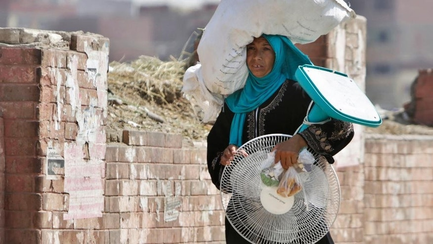 An Egyptian farmer carries an electric fan as she walks through a Cairo street , Egypt, Tuesday, Aug. 11, 2015. Egyptian health authorities say at least 40 people have died in the last two days amid a scorching heatwave hitting the country. (AP Photo/Amr Nabil)
