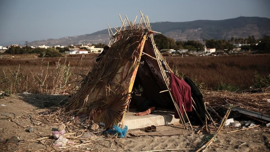 A migrant sleeps inside a makeshift hut which have been set up outside an abandoned hotel where dozens of migrants have been living the last weeks at Kos town, on the southeastern island of Kos, Monday, Aug. 10, 2015. The European Union is granting 2.4 billion euros/$2.6 billion to EU nations to upgrade their migration programs with the biggest sums going to Greece and Italy where thousands of refugees have arrived this year. (AP Photo/Yorgos Karahalis)