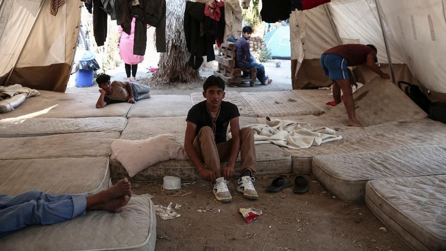 A migrant ties his laces inside a tent which have been set up at the premises of an abandoned hotel where dozens of migrants have been living the last weeks at Kos town, on the southeastern island of Kos, Monday, Aug. 10, 2015. The European Union is granting 2.4 billion euros/$2.6 billion to EU nations to upgrade their migration programs with the biggest sums going to Greece and Italy where thousands of refugees have arrived this year. (AP Photo/Yorgos Karahalis)