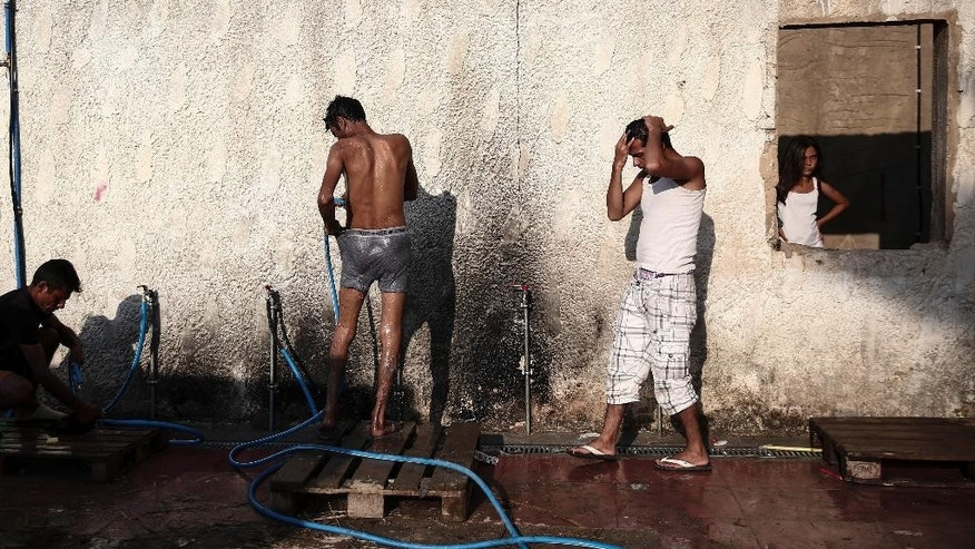 Migrants wash themselves outside an abandoned hotel where dozens of migrants have been living the last weeks at Kos town, on the southeastern island of Kos, Monday, Aug. 10, 2015. The European Union is granting 2.4 billion euros/$2.6 billion to EU nations to upgrade their migration programs with the biggest sums going to Greece and Italy where thousands of refugees have arrived this year.(AP Photo/Yorgos Karahalis)