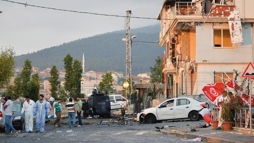 Turkish police officers work at the site of an explosion at a police station, seen right, in Istanbul's Sultanbeyli neighborhood, early Monday, Aug. 10, 2015. The bomb attack injured three policemen and seven civilians and caused a fire that collapsed part of the three-story building. Police said the assailants exploded a car bomb near the station. Unknown assailants later fired on police inspecting the scene of the explosion, sparking another gunfight with police that killed a member of the police inspection team and two assailants. (AP Photo/Akin Celiktas)