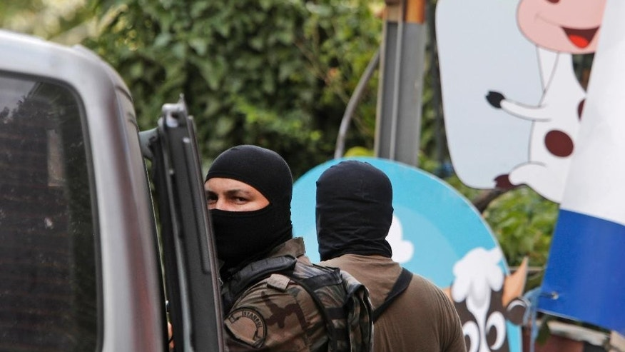 Masked Turkish police officers secure a road leading to the U.S. Consulate building in Istanbul, Monday, Aug. 10, 2015. Two assailants opened fire at the building on Monday, touching off a gunfight with police before fleeing the scene, Turkish media reports said. (AP Photo/Lefteris Pitarakis)