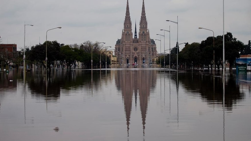 The Basilica is reflected in flood water in Lujan, Argentina, Tuesday, Aug. 11, 2015. Heavy weekend rains caused rivers to rise precipitously in Argentina's Buenos Aires province. (AP Photo/Natacha Pisarenko)