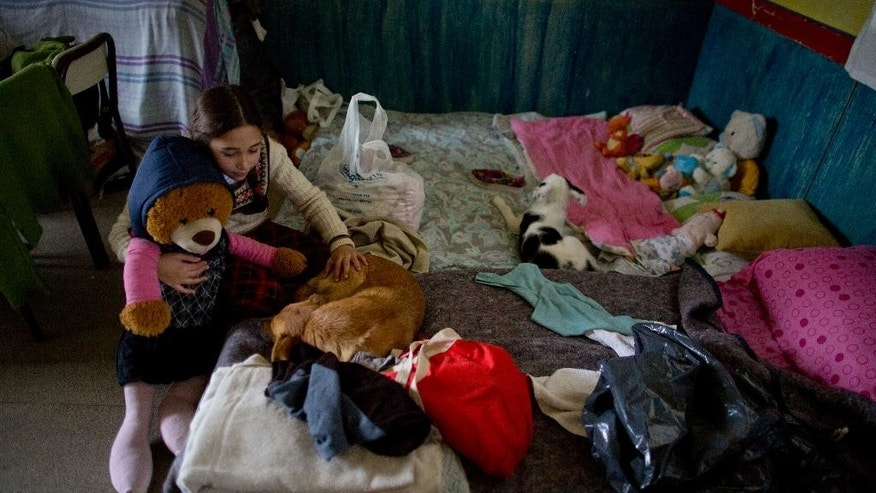 Flavia Cordoba holds her stuffed animal as she pets her dog inside a shelter for families whose homes flooded in Lujan, Argentina, Tuesday, Aug. 11, 2015. Thousands of people are evacuating parts of Argentina's Buenos Aires province after heavy weekend rains caused rivers to rise precipitously. (AP Photo/Natacha Pisarenko)