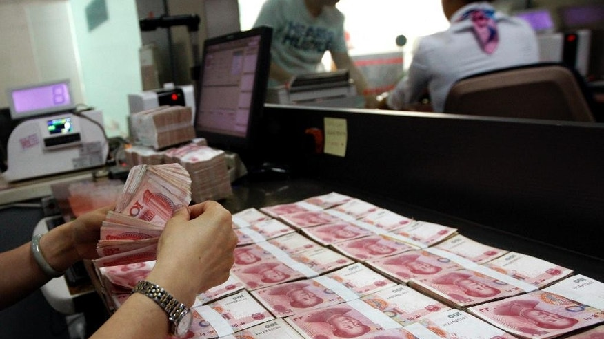 In this Tuesday, Aug. 11, 2015 photo, a bank clerk counts Chinese currency notes as her colleague attends a customer at a bank outlet in Huaibei in central China's Anhui province. China's surprise move on Tuesday to devalue its currency has intensified concerns about a slowdown in the world's second-largest economy, whose growth rate has reached a six-year low. It is also fanning tensions with the United States and Europe, whose exports could become comparatively costlier. (Chinatopix via AP) CHINA OUT