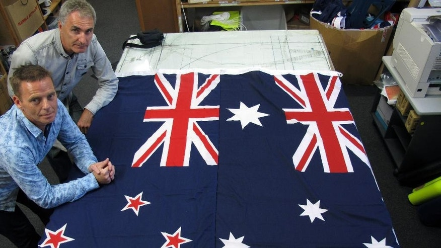 FILE - In this March 3, 2014, file photo, Victor Gizzi, left, and David Moginie, managers at flag manufacturer Flagmakers, pose next to flags of New Zealand, left, and Australia, in their factory near Wellington, New Zealand. Many consider the current flag to be outdated and too similar to Australia's flag. It depicts Britain's Union Jack in the top left corner, which harks back to a colonial past that many New Zealanders are eager to put behind them. New Zealand sometimes comes under the shadow of its larger neighbor, Australia, and having flags that are almost identical only compounds that problem. New Zealand is considering changing its flag. (AP Photo/Nick Perry, File)