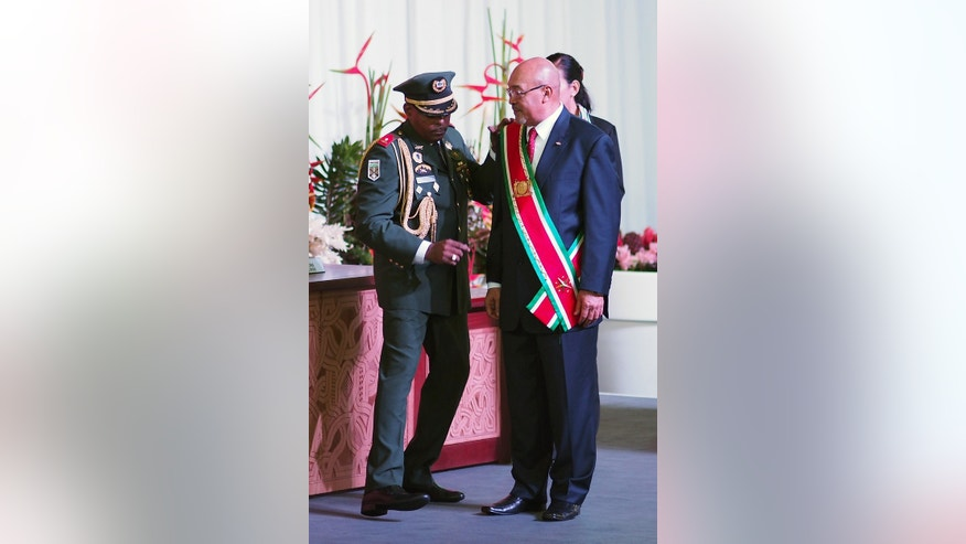 Suriname's President Desi Bouterse, re-elected to a second, five-year term, receives the presidential sash during his inauguration ceremony in Paramaribo, Suriname, Wednesday, Aug. 12, 2015. A  two-time coup leader and former dictator accused of executing 15 political opponents in 1982, Bouterse obtained immunity as head of state when he was democratically elected in 2010 amid widespread discontent with Suriname's economy. (AP Photo/Ertugrul Kilic)