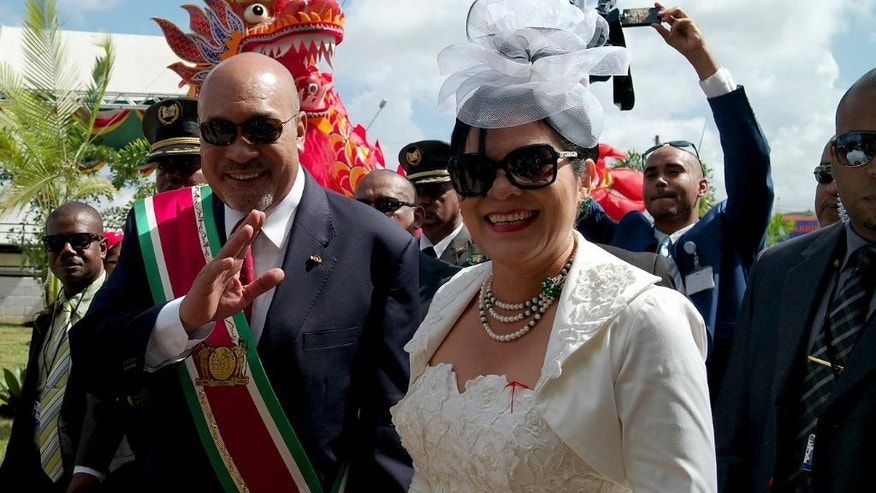 Suriname President Desire Delano Bouterse arrives to his second term inaugural ceremony with his wife, first lady Ingrid Bouterse-Waldring, in Paramaribo, Suriname, Wednesday, Aug. 12, 2015. A two-time coup leader and former dictator accused of executing 15 political opponents in 1982, Bouterse obtained immunity as head of state when he was democratically elected in 2010 amid widespread discontent with Suriname's economy. (AP Photo/Ertugrul Kilic)