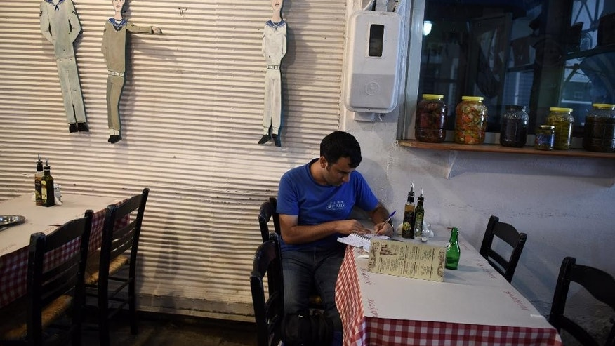 A restaurant employee writes on a paper at the northern Greek port city of Thessaloniki, Tuesday, Aug. 11, 2015. Greece has agreed on the broad terms of a new three-year bailout package with international creditors, with only a few details left to iron out, the finance minister said Tuesday.(AP Photo/Giannis Papanikos)