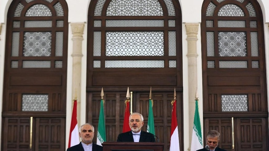 Iranian Foreign Minister Mohammad Javad Zarif, center, speaks during a press conference at the government palace in Beirut, Lebanon, Tuesday, Aug. 11, 2015. Zarif is holding talks with Lebanese officials before proceeding on to Damascus, Syria. (AP Photo/Bilal Hussein)