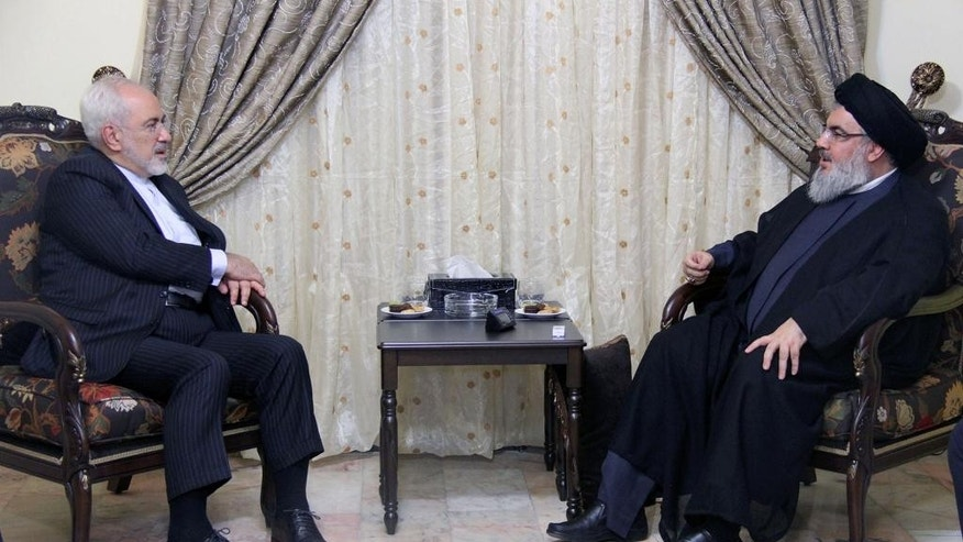In this picture released by the Hezbollah media department, Hezbollah leader Sheik Hassan Nasrallah, right, meets with Iranian Foreign Minister Mohammad Javad Zarif, left, in Beirut, Lebanon, Wednesday, Aug. 12, 2015. The television station of Lebanon's militant Hezbollah group says its leader has discussed attempts to find a resolution to Syria's civil war with Iranian Foreign Minister Mohammad Javad Zarif. (Hezbollah Media Department via AP)