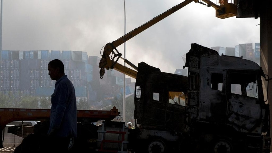 A man walks past a worker inspecting the damage to a light rail system caused by an explosion in northeastern China's Tianjin municipality, Thursday, Aug. 13, 2015. Chinese state media reported huge explosions at the Tianjin port late Wednesday. (AP Photo/Ng Han Guan)