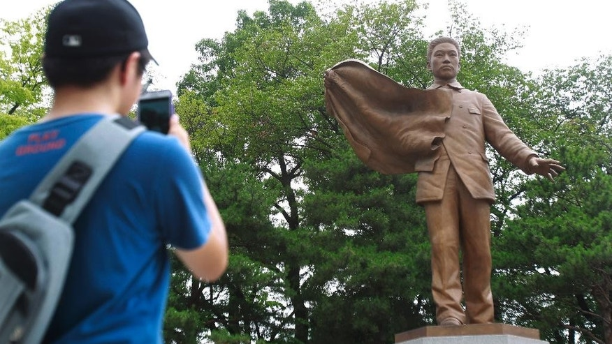In this July 21, 2015 photo, a South Korean visitor takes picture of a statue of South Korean patriot Ahn Jung-geun, who shot down Japan's former top official in Korea, Ito Hirobumi, in 1909, the year before occupying Tokyo formally annexed the Korean Peninsula, at Ahn Jung-geun memorial hall in Seoul, South Korea. Perhaps the crystallization of abysmal Japan-South Korea ties can be found in the widespread veneration of Ahn. A young, mustachioed Ahn, cradling a hand disfigured when he sliced off part of a finger as an expression of patriotism, can be seen on banners and posters throughout Seoul.  (AP Photo/Julie Yoon)