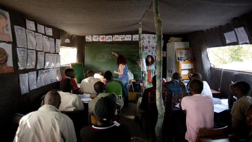 "In this Friday, Aug. 7, 2015, photo, volunteer teacher Delphine Blain teaches French to immigrants at a makeshift school set at camp near Calais, northern France. The floor is sandy like the nearby dunes, the canvas roof is held by tree branches covered in flowered cloth and the students seated at small desks are listening with soldierly attention. The single-room schoolhouse on one edge of Calais' vast and squalid migrant camp known as the ""jungle"" would seem like a mirage, except that the four to six classes per day are packed with students. (AP Photo/Emilio Morenatti)"