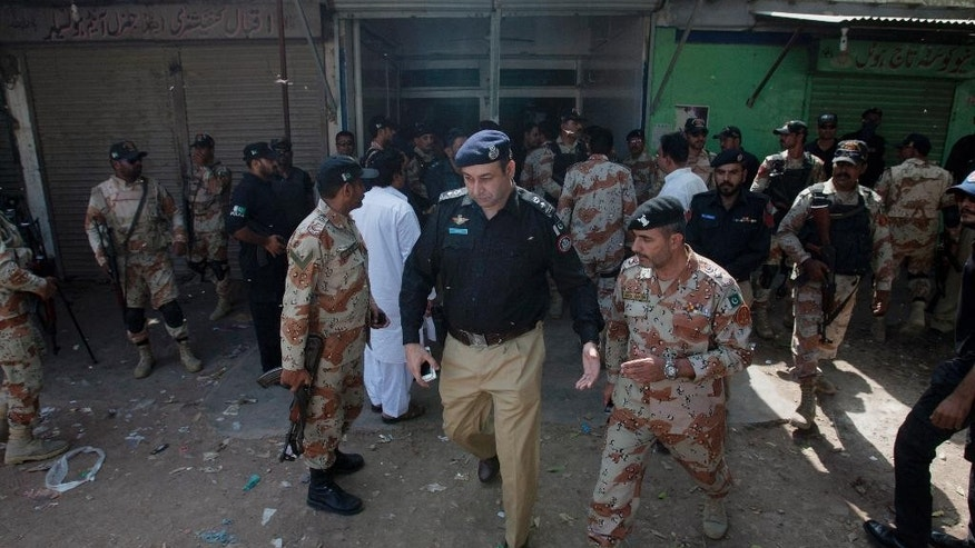 Police and paramilitary troops surround a restaurant following a deadly attack on police officers in Karachi, Pakistan, Wednesday, Aug. 12, 2015. A police officer said gunmen killed several policemen at the roadside restaurant in southern Pakistan. (AP Photo/Shakil Adil)