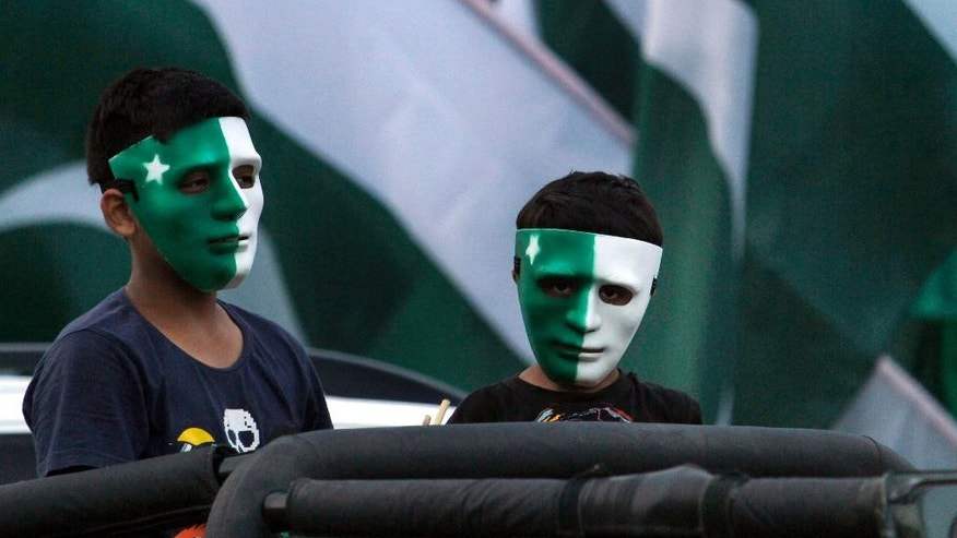 Pakistani youngsters wear masks painted in the design of the national flag after buying it from a stall to celebrate the country's upcoming 69th Independence Day in Islamabad, Pakistan, Wednesday, Aug. 12, 2015. Millions of Pakistanis will hold rallies for Independence Day on Friday to commemorate its independence in 1947 from British colonial rule. (AP Photo/Anjum Naveed)