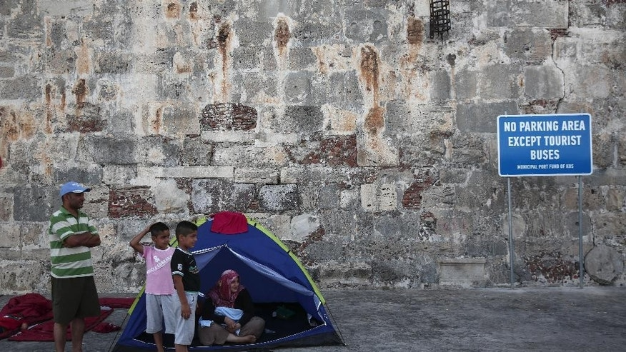 Migrants stand outside their tent in front of a castle at Kos town, on the southeastern island of Kos, Tuesday, Aug. 11, 2015. Overwhelmed police clerks used fire extinguishers and batons Tuesday to control hundreds of boat people jostling to be registered in the Greek island's tourist-filled main port, where thousands have been sleeping rough for days waiting for temporary travel documents. (AP Photo/Yorgos Karahalis)