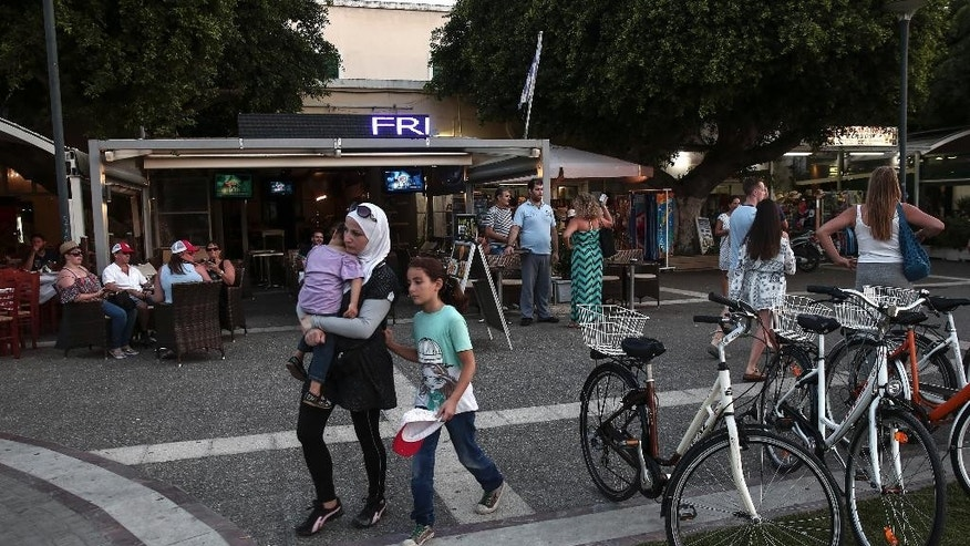 Migrants make their way at a tourist area of Kos town, on the southeastern island of Kos, Tuesday, Aug. 11, 2015. Overwhelmed police clerks used fire extinguishers and batons Tuesday to control hundreds of boat people jostling to be registered in the Greek island's tourist-filled main port, where thousands have been sleeping rough for days waiting for temporary travel documents. (AP Photo/Yorgos Karahalis)