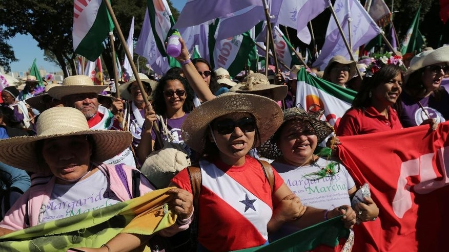 Women from across Brazil take part in the March of the Daisies in Brasilia, Brazil, Wednesday, Aug. 12, 2015. The annual women's march is an act to support the rights of agriculture workers and their communities, as well a protest against inequality and gender violence. (AP Photo/Eraldo Peres)