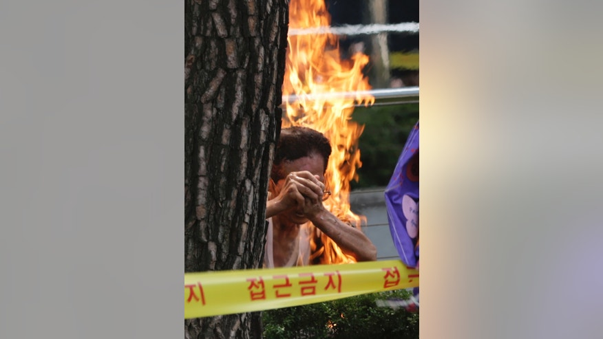 EDITOR'S NOTE: GRAPHIC CONTENT A South Korean man sets himself on fire during an anti-Japan rally demanding full compensation and an apology for wartime sex slaves from the Japanese government in front of the Japanese Embassy in Seoul, South Korea, Wednesday, Aug. 12, 2015. Rescue worker Woo Kyung-suk said that the 80-year-old man sustained third-degree burns on his upper body and arms and was breathing when he was carried into an emergency vehicle. The man's motives weren't immediately clear. (AP Photo/Lee Jin-man)
