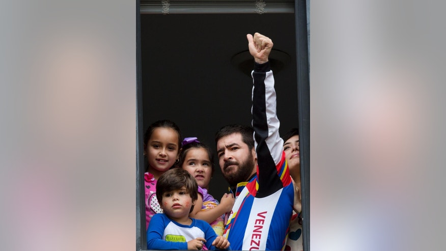 Daniel Ceballos, former mayor of the western city of San Cristobal, gestures from an apartment window with his daughters, Maria Veronica, top left, Maria Daniel, who he holds, son Juan Daniel and wife Patricia de Ceballos, as they look out toward supporters and members of the press in Caracas, Venezuela, Wednesday, Aug. 12, 2015. One of Venezuela's most prominent opposition leaders started his first day of house arrest Wednesday after a surprise release following a year and a half in prison. (AP Photo/Ariana Cubillos)