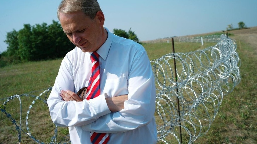 Robert Molnar, mayor of the southern Hungarian village of Kubekhaza looks at the razor wire installed onto the Hungarian - Serbian border near Kubekhaza, Hungary on Wednesady Aug. 12, 2015. Molnar whose village Kubekhaza is at the end of a fence being built on the Serbian border says the barrier is a government effort to win back voters from the far-right Jobbik party and migrants will just try to circumvent it. Molnar, a former lawmaker, says that while migration is a serious problem for Europe, migrants should be treated with leniency. (AP Photo/Bela Szandelszky)