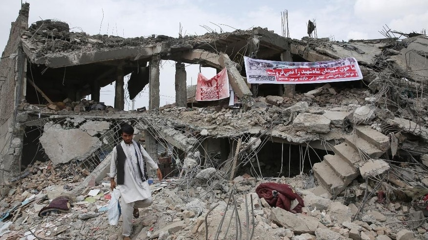 An Afghan man walks through the debris of a market destroyed by the blast of last Friday's truck bomb in Kabul, Afghanistan, Thursday, Aug. 13, 2015. The Afghan government on Thursday sent a high-level delegation to Pakistan to discuss an action plan after Islamabad-hosted peace talks with the Taliban were suspended last month, officials said. Arabic on banner reads: We will not sell out our Shah Shahid's martyrs' blood. We want to know all secrets of this mysterious attack. (AP Photo/Massoud Hossaini)