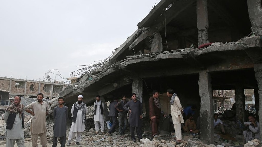 Afghan residents stand near the debris of a market destroyed by the blast of last Friday's truck bomb in Kabul, Afghanistan, Thursday, Aug. 13, 2015. The Afghan government on Thursday sent a high-level delegation to Pakistan to discuss an action plan after Islamabad-hosted peace talks with the Taliban were suspended last month, officials said. (AP Photo/Massoud Hossaini)
