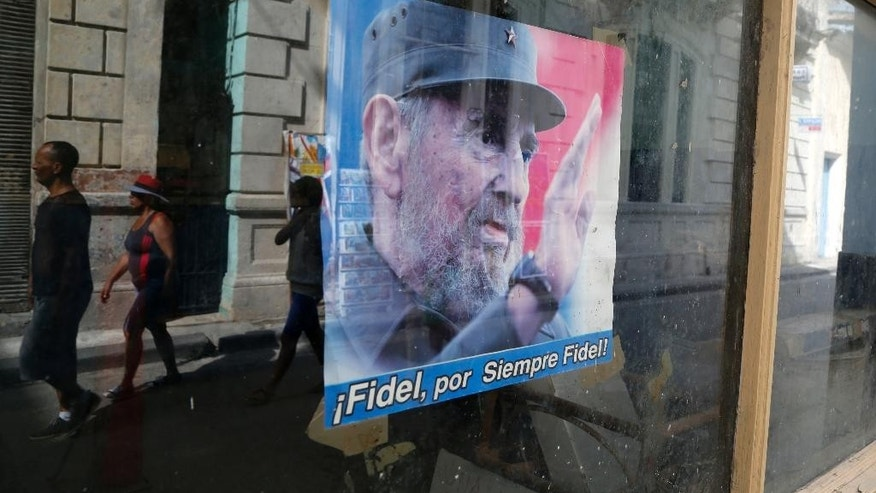 "FILE - In this July 4, 2015 file photo, a poster of Fidel Castro with a message that reads in Spanish: ""Fidel, forever Fidel!"" decorates the administrative office window of state-run food stores, in Havana, Cuba. Castro is celebrating his 89th birthday, Thursday, Aug. 13, 2015, with a newspaper column repeating assertions that the U.S. owes socialist Cuba ""numerous millions of dollars"" for damages caused by a decades-long embargo. (AP Photo/Desmond Boylan, File)"