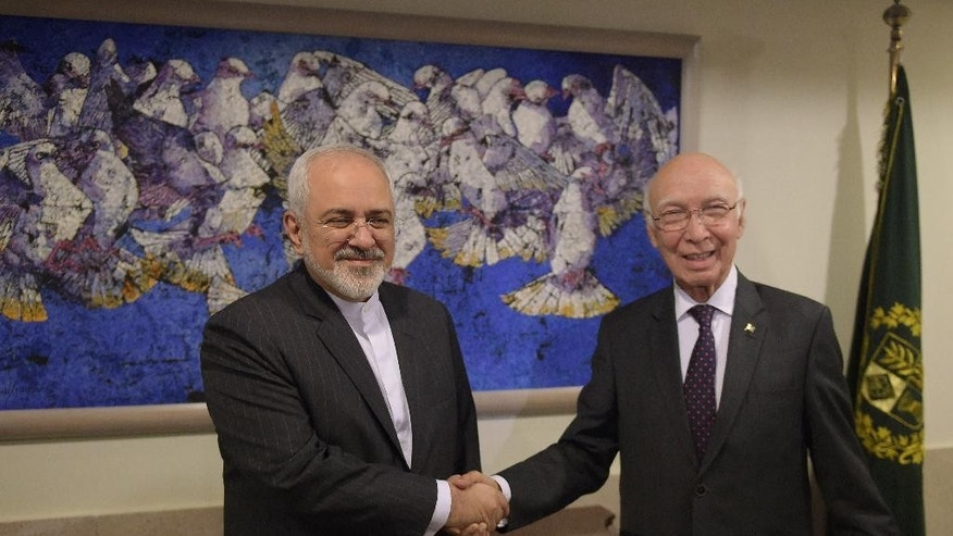 Pakistan's National Security Advisor Sartaj Aziz, right, shakes hands with Iranian Foreign Minister Javad Zarif at the Foreign Ministry in Islamabad Thursday, Aug. 13, 2015. Zarif arrived in Islamabad to meet with Pakistani leaders. (Aamir Qureshi/Pool Photo via AP)
