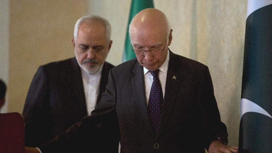 Pakistan's Prime Minister's Adviser on Foreign Affairs Sartaj Aziz, right, leaves after addressing a news conference with his Iranian counterpart Foreign Minister, Mohammad Javad Zarif, at the Foreign Ministry in Islamabad, Pakistan, Thursday, Aug. 13, 2015. (AP Photo/B.K. Bangash)