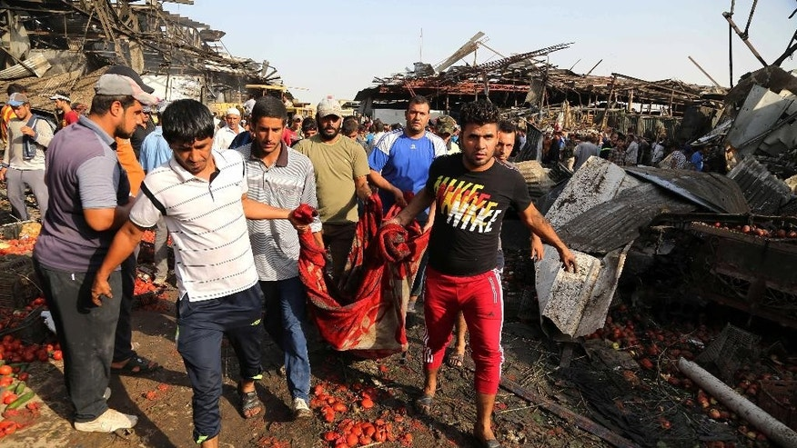 People evacuate the body of a victim killed from a bombing in Jameela market in the Iraqi capital's crowded Sadr City neighborhood Baghdad, Iraq, Thursday, Aug. 13, 2015. A massive truck bomb ripped through a popular Baghdad food market in a predominantly Shiite neighborhood in the early morning hours on Thursday, killing at least 58 people, police officials said. (AP Photo/Karim Kadim)