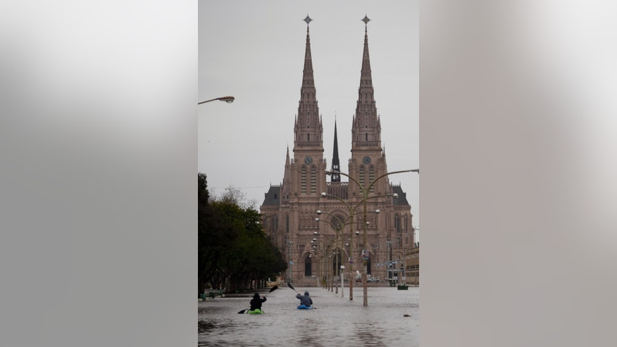 Two men paddle their kayaks on a flooded street near the Basilica in Lujan, Argentina, Wednesday, Aug. 12, 2015. More than 11,000 people had been evacuated by Tuesday from parts of Argentina's largest province after heavy weekend rains caused rivers to rise precipitously, a top official said. (AP Photo/Natacha Pisarenko)