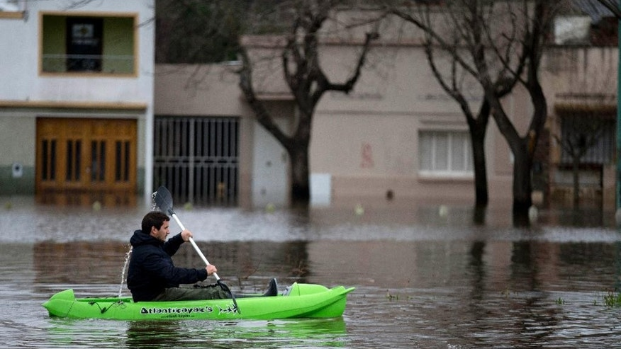 A man paddles his kayak on a flooded street in Lujan, Argentina, Wednesday, Aug. 12, 2015. More than 11,000 people had been evacuated by Tuesday from parts of Argentina's largest province after heavy weekend rains caused rivers to rise precipitously, a top official said. (AP Photo/Natacha Pisarenko)