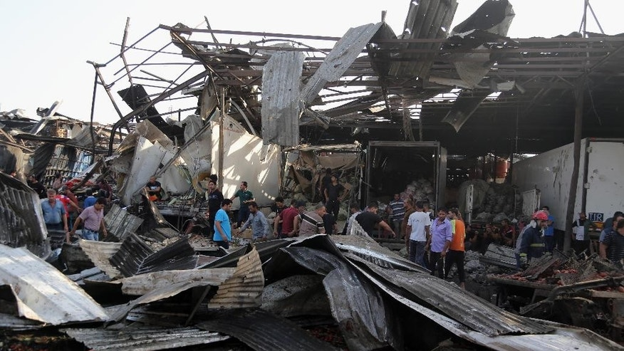 Civilians gather at the scene of bomb attack in Jameela market in the Iraqi capital's crowded Sadr City neighborhood Baghdad, Iraq, Thursday, Aug. 13, 2015. A massive truck bomb ripped through a popular Baghdad food market in a predominantly Shiite neighborhood in the early morning hours on Thursday, killing dozens of people, police officials said. (AP Photo/Karim Kadim)