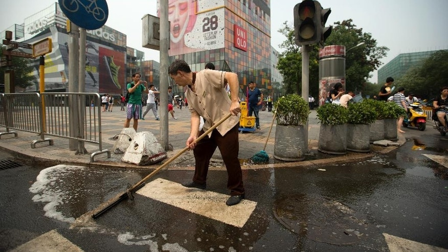 A maintenance worker cleans the spot where a woman was stabbed to death in Beijing, Thursday, Aug. 13, 2015. A man slashed a woman to death and injured her French companion in one of Beijing's busiest shopping districts in broad daylight Thursday, police said. (AP Photo/Mark Schiefelbein)