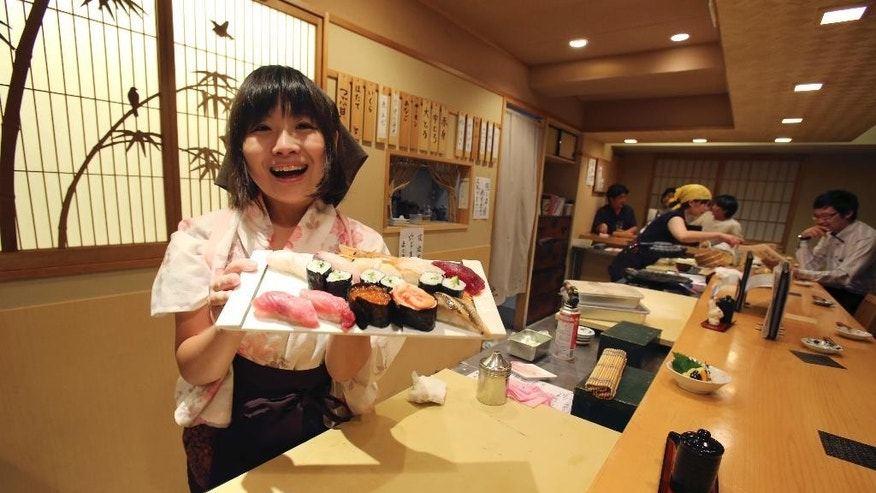 "In this Aug. 3, 2015 photo, Yuki Chidui, sushi chef and manager at Nadeshico sushi restaurant, shows off a set of sushi she made at her all-women restaurant in Tokyo. Deeply rooted stereotypes such as the so-called ""Edo-style"" macho demeanor of sushi chefs and belief that warmer body temperature of women leads to inferior taste have kept sushi preparation an almost exclusively male domain in Japan. But some women are out to challenge tradition and are learning the art of sushi at a time when the government is emphasizing a greater role for women to offset Japan's shrinking workforce. (AP Photo/Koji Sasahara)"
